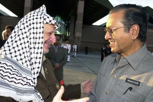 Malaysian Prime Minister Mahathir Mohamad (R) greets visiting Palestinian leader Yasser Arafat on 25 August 2001 in Kuala Lumpur. [Getty Images]