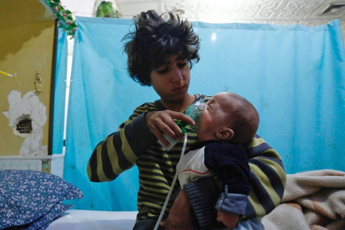 A Syrian boy holds an oxygen mask over the face of an infant at a make-shift hospital following a reported gas attack on the rebel-held besieged town of Douma in the eastern Ghouta region on the outskirts of the capital Damascus on January 22, 2018 [HASAN MOHAMED/AFP via Getty Images]