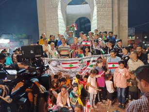Palestinian children in Gaza lighting candles at a special programme in Gaza City. Palestinian and Lebanese flags were displayed side by side [Hasan Eslayeh]