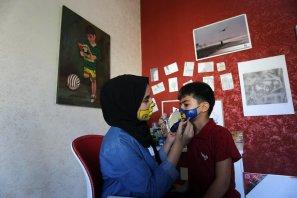 Palestinian painter, Raneen Al-Zuraie, 18, paints masks on children's faces, amid the coronavirus disease (COVID-19), in Deir Al-Balah, in the central Gaza Strip, on September 15, 2020. [Ashraf Amra/Apaimages]