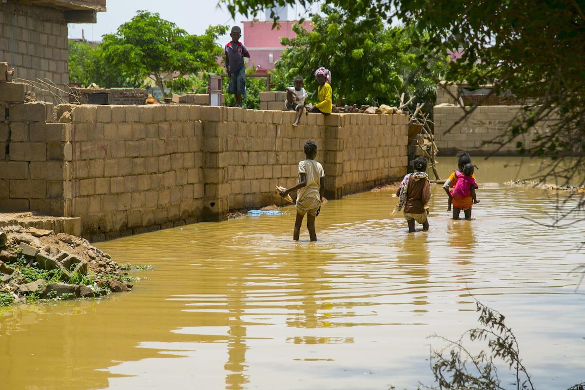 Sudanese children wade through a flooded street at al-Qalqili district in Khartoum, Sudan on 29 August 2020. [Mahmoud Hjaj - Anadolu Agency]