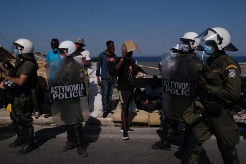 Police officers stand during the protest against the living conditions in the Moria refugee camp on the Greek island of Lesbos in Greece on September 11, 2020 [Aggelos Barai - Anadolu Agency]