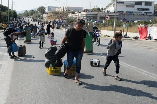 Refugees carry their belongings as they move to a new camp on the Greek island of Lesbos, on 17 September 2020 [Grigoris Siamidis/Anadolu Agency]