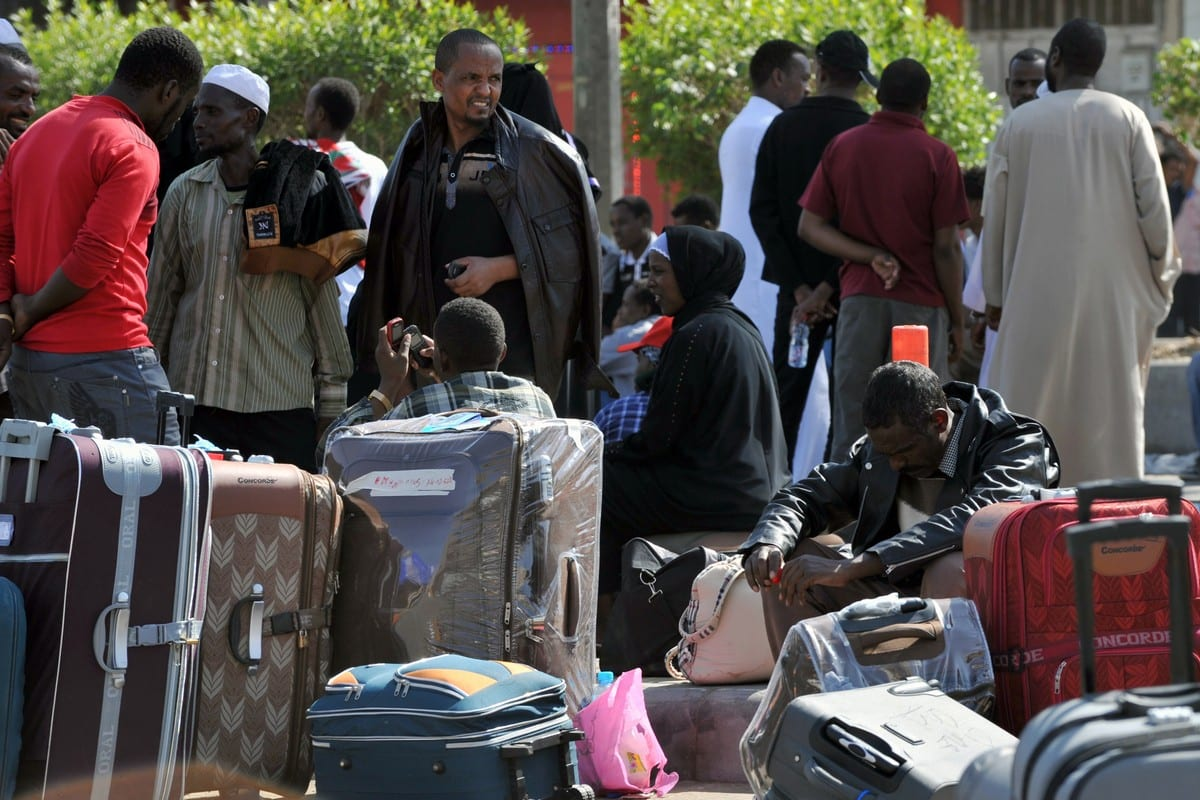 Foreign workers wait with their belongings before boarding police buses transferring them to a deportation centre in Riyadh, Saudi Arabia on 14 November 2013 [FAYEZ NURELDINE/AFP/Getty Images]