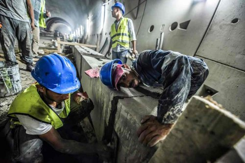 Labourers apply cement as they carry out construction work on a new twin-tube road tunnel along the Suez Canal in the Egyptian city of Ismailia on September 4, 2018. [KHALED DESOUKI/AFP via Getty Images]