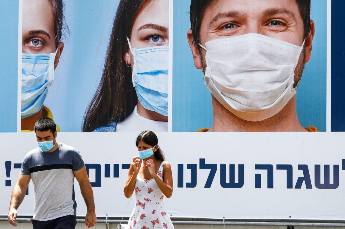 A mask-clad man and woman walk past a billboard showing other mask-clad faces and adequate social distance measures, raising awareness about COVID-19 coronavirus pandemic precautions, in the centre of the Israeli city of Ramat Gan, east of Tel Aviv, on July 17, 2020 [JACK GUEZ/AFP via Getty Images]