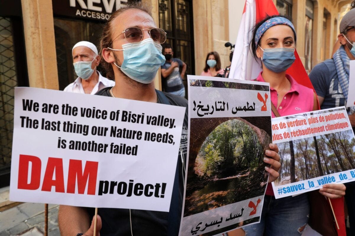 Demonstrators hold placards as they take part in a rally in front of the World Bank offices in the downtown district of the Lebanese capital Beirut on July 25, 2020, to protest against the Bisri dam project [ANWAR AMRO/AFP via Getty Images]
