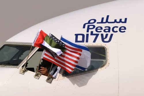 "The Emirati, Israeli and US flags are picture attached to an air-plane of Israel's El Al, adorned with the word ""peace"" in Arabic, English and Hebrew, upon it's arrival at the Abu Dhabi airport in the first-ever commercial flight from Israel to the UAE, on August 31, 2020 [KARIM SAHIB/AFP via Getty Images]"