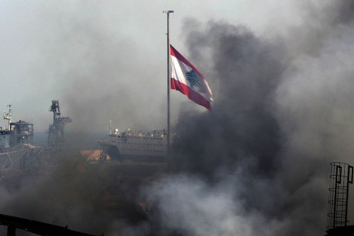 A Lebanese flag flutters amid billowing smoke as firefighters extinguish the remaining flames at the seaport of Beirut, on 11 September 2020 [ANWAR AMRO/AFP/Getty Images]