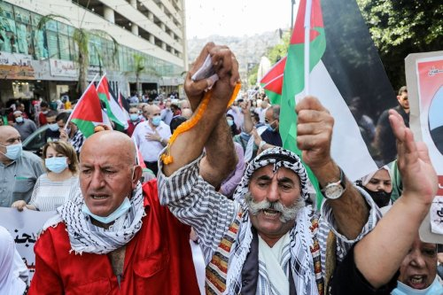 Demonstrators, mask-clad due to the COVID-19 coronavirus pandemic, demonstrate with Palestinian flags during a protest against the United Arab Emirates' and Bahrain's decisions to normalise relations with Israel, in the city of Nablus in the occupied West Bank on September 15, 2020. - [JAAFAR ASHTIYEH/AFP via Getty Images]