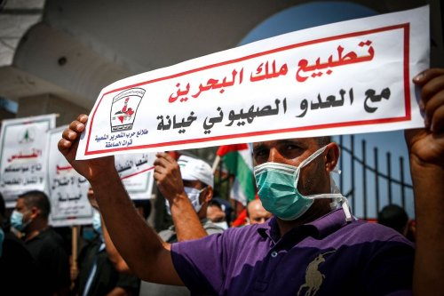 "A demonstrator holds a sign in Arabic meaning ""the King of Bahrain's normalisation with Israel is betrayal"" during a protest against normalising relations with Israel on 15 September 2020 [MOHAMMED ABED/AFP/Getty Images]"