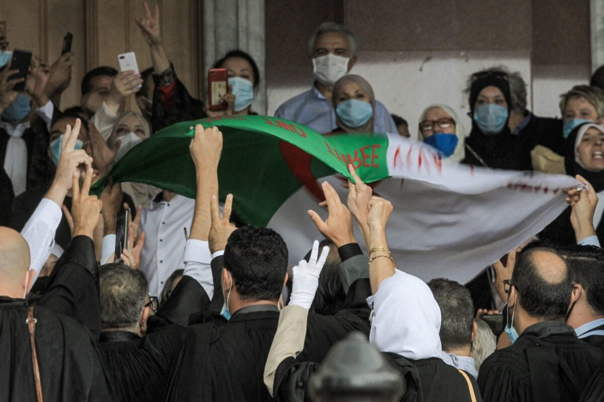 """Lawyers, mask-clad due to the COVID-19 coronavirus pandemic, chant slogans and wave an Algerian national flag as they demonstrate outside the Court of Algiers in Algeria's capital on September 27, 2020 calling for the """"independence of the judiciary"""". (Photo by - / AFP) (Photo by -/AFP via Getty Images)"""
