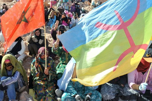 Women carrying a Moroccan (L) and an Amazigh flag (R) and flashing the three-finger Amazigh symbol during a sit-in on March 2, 2012 [ABDELHAK SENNA/AFP via Getty Images]