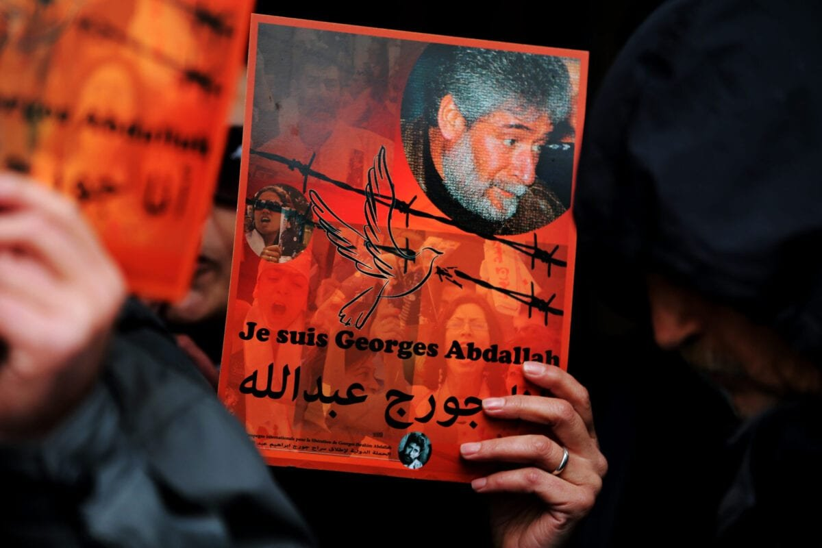 A supporter of Lebanese militant Georges Ibrahim Abdallah holds up a placard bearing his portrait and a slogan in French and Arabic reading: 'I am Georges Abdallah' during a protest outside the French embassy in Beirut demanding his release on February 20, 2015. [JOSEPH EID/AFP via Getty Images]