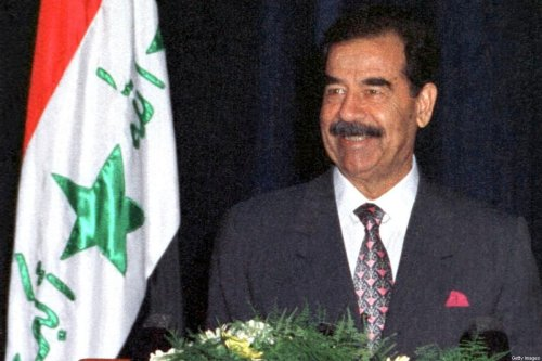 A smiling Iraqi President Saddam Hussein gives a speech 17 July 1999 in Baghdad, during celebrations marking the 31st anniversary of the Baath party revolution in Iraq. [AFP via Getty Images]