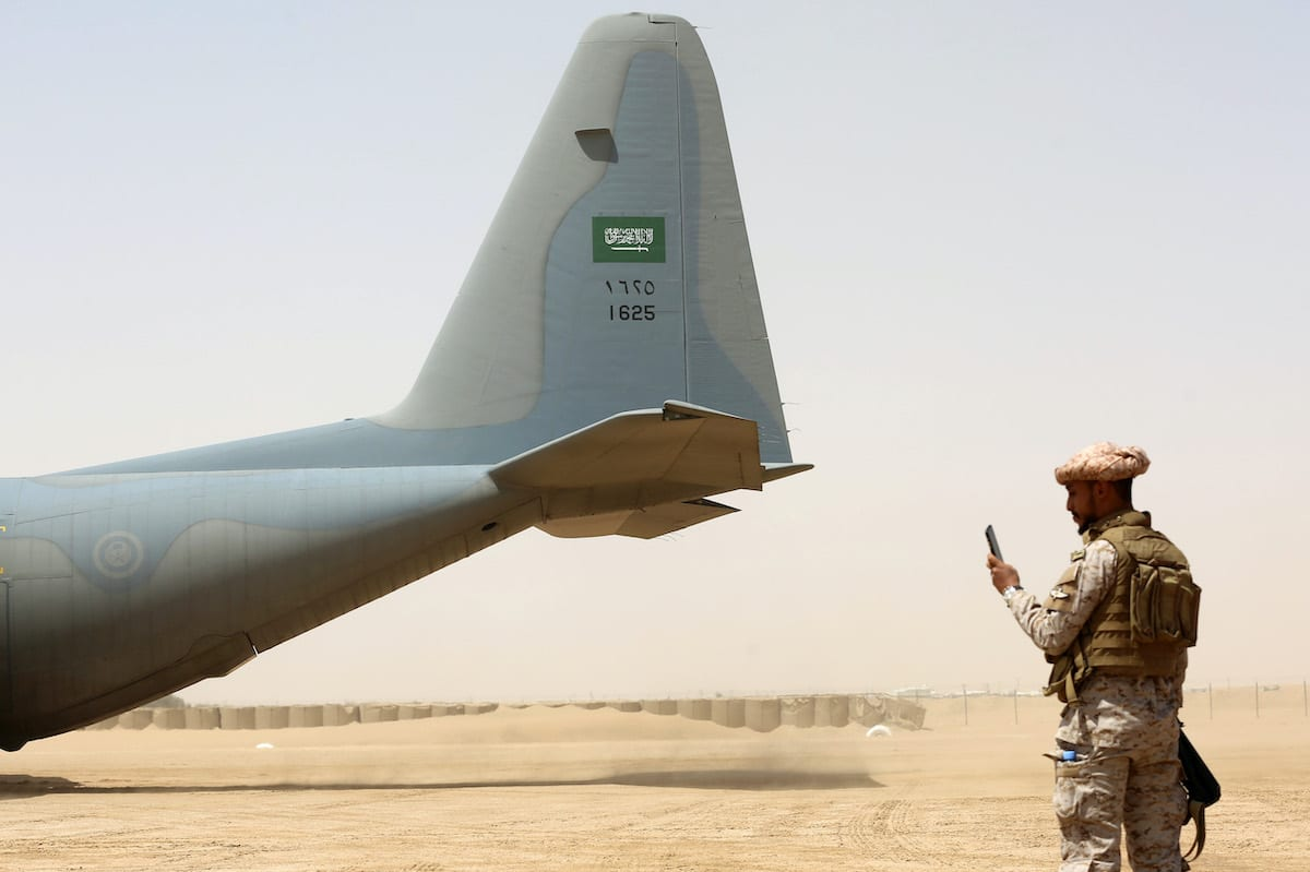 A Saudi soldier stands guard before aid supplies are unloaded from a Saudi air force cargo plane at an airfield in Yemen's central province of Marib, on 12 March 2018. [ABDULLAH AL-QADRY/AFP via Getty Images]