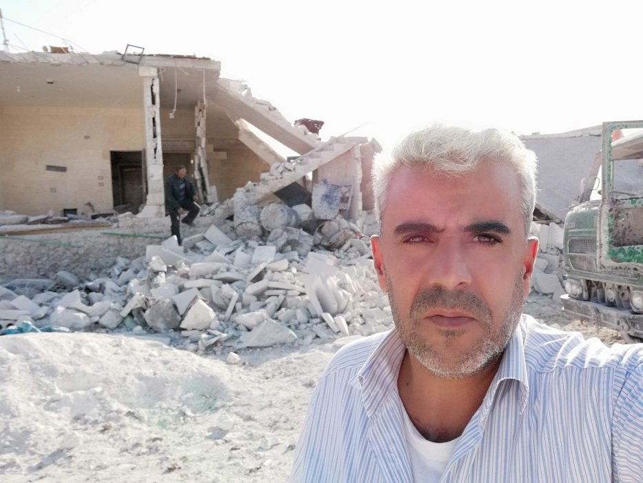 Dergham Hammadi in front of a civilian home bombed by the regime