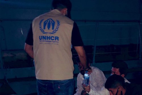 A UNHCR worker with asylum seekers who were at sea, 22 September 2020 [UNHCRLibya/Twitter]