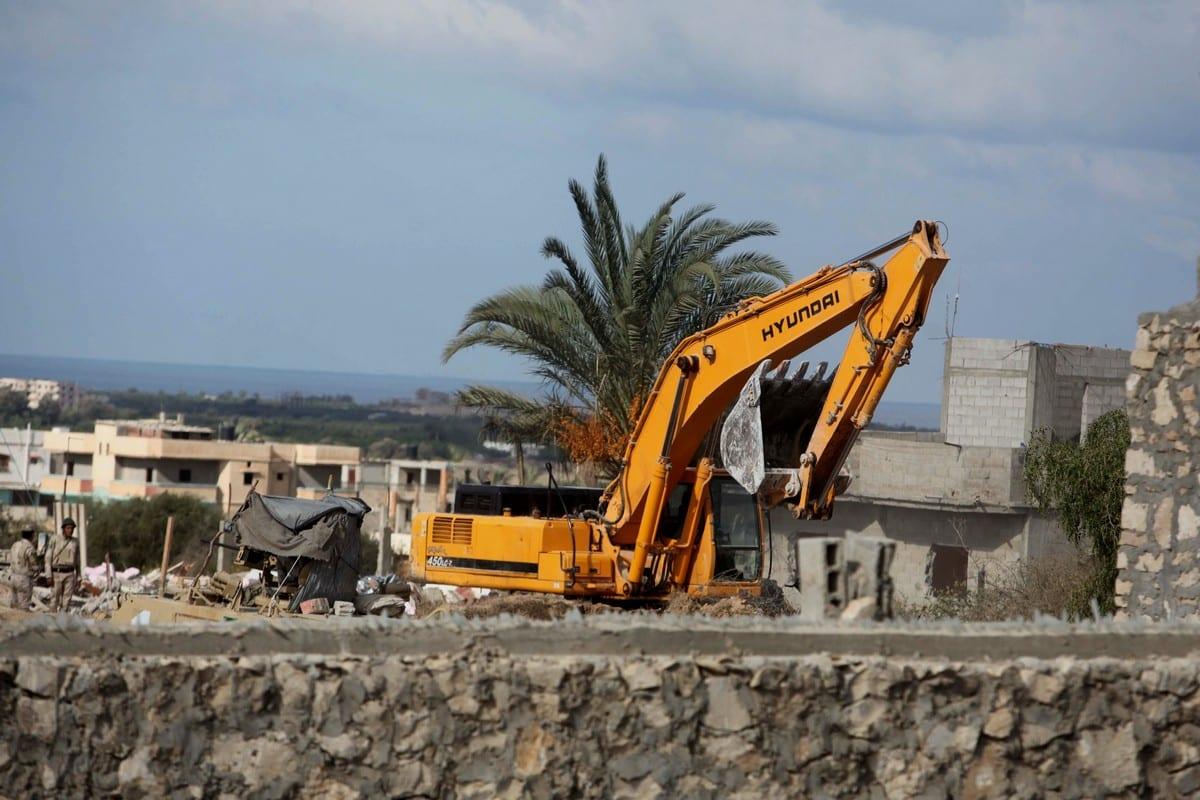 Egyptian security forces use a bulldozer to demolish a house on 30 October 2014 [Ashraf Amra/ApaImages]