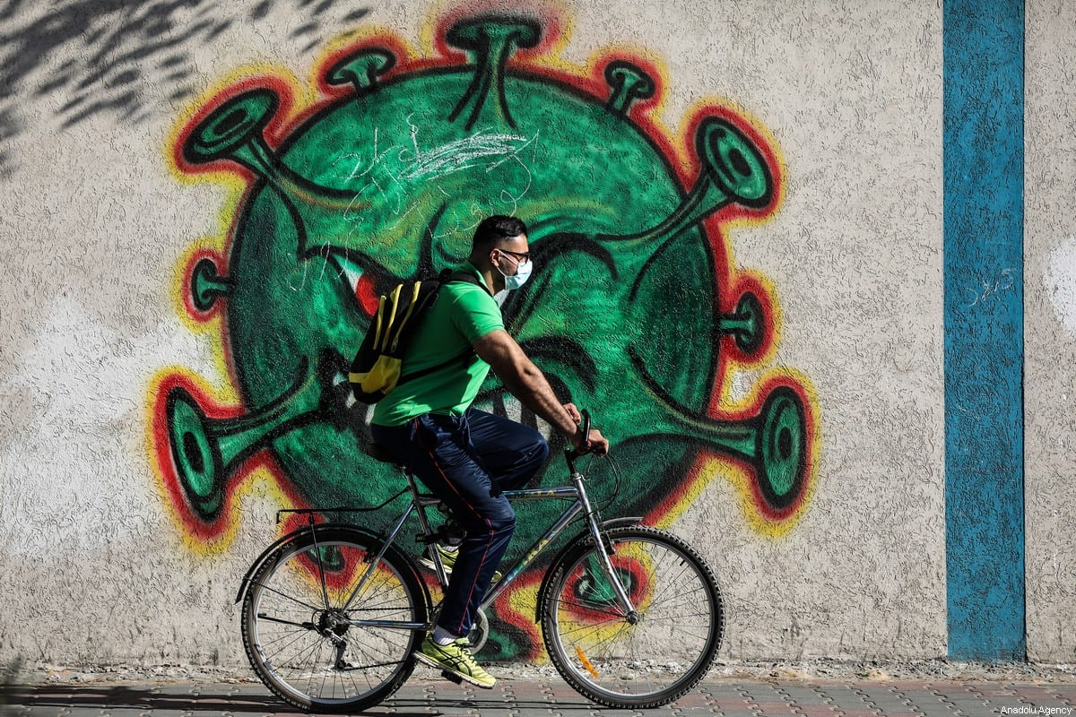 A man wearing a face mask rides past a mural depicting of a virus to draw attention and raise awareness to the fight against the novel coronavirus (COVID-19) pandemic in Gaza Strip, Gaza on 3 October 2020. [Mustafa Hassona - Anadolu Agency]