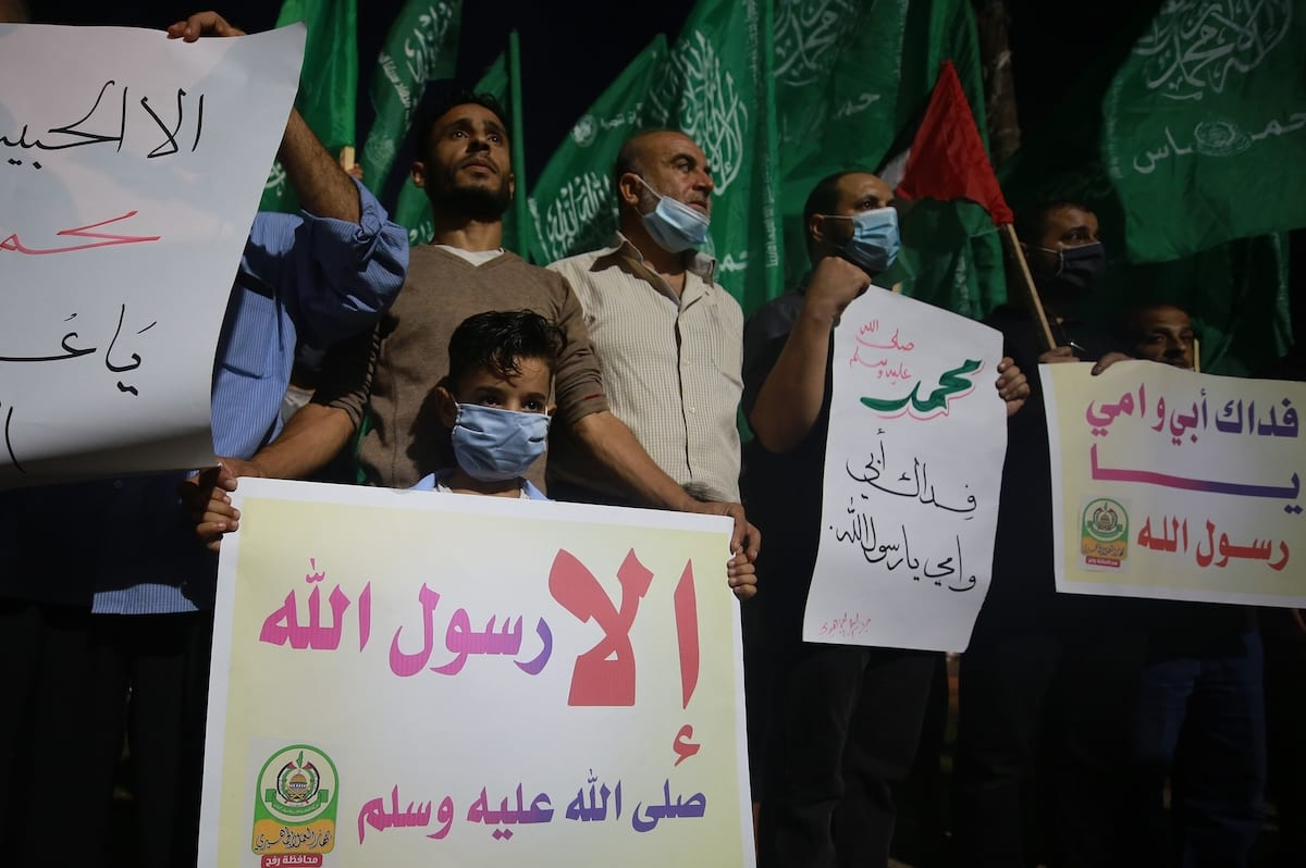 Palestinians gather to stage a protest against the republication of offensive caricatures of the Prophet Muhammad in France and the statement of French President Emmanuel Macron, in Rafah, Gaza on 24 October 2020. [Mustafa Hassona - Anadolu Agency]