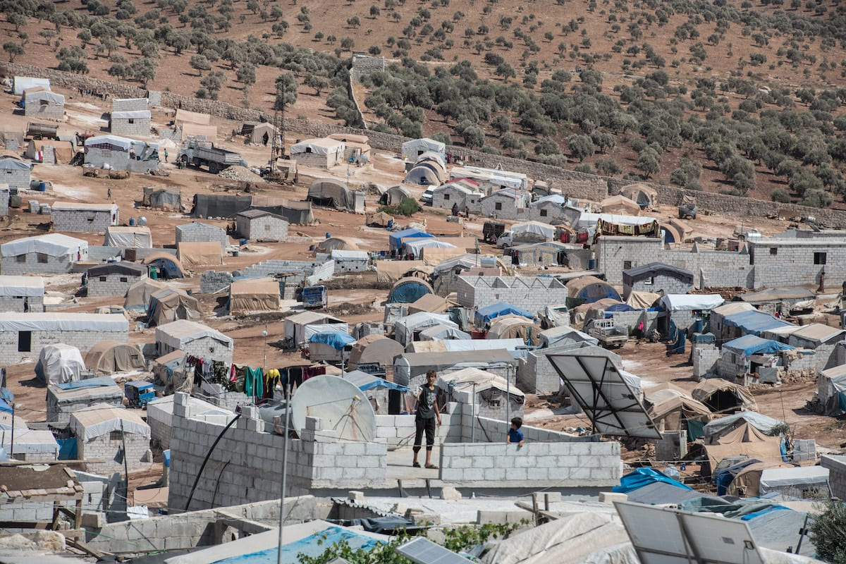 A displaced Syrian boy stands on a rooftop of his home at the village of Atmeh which hosts nearly 1 million displaced Syrians near the Syrian-Turkish border in Idlib Province September 17, 2019 [Burak Kara/Getty Images]