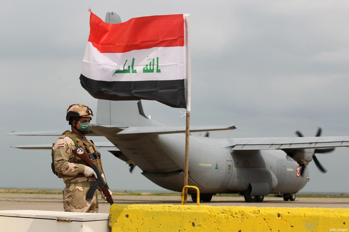 An Iraqi soldiers stands guard in front US military air carrier at the Qayyarah air base, in Iraq [AHMAD AL-RUBAYE/AFP via Getty Images]