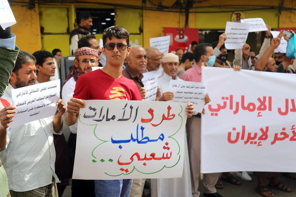 "A Yemeni protester holds a sign reading in Arabic ""evicting the Emirates is a national demand"", during a demonstration against the United Arab Emirates and the Southern Transitional Council (STC) in the country's third city of Taez on 24 June 2020, [AHMAD AL-BASHA/AFP via Getty Images]"