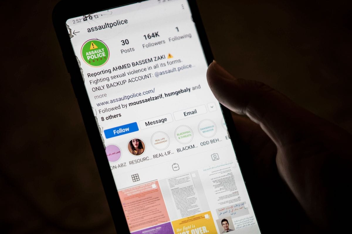 A woman checks on her phone an Instagram account for reporting allegations of sexual harassment and misconduct against Ahmed Bassam Zaki, a 22-year-old student, in Cairo on 15 July 2020. [KHALED DESOUKI/AFP via Getty Images]