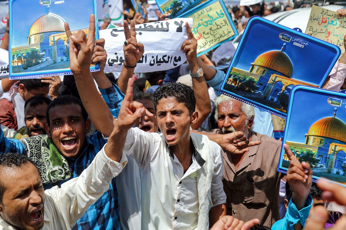 """Demonstrators chant slogans with signs depicting Jerusalem's Dome of the Rock alongside other signs reading in Arabic """"no to normalisation with the Zionist entity"""", during a protest in Yemen's third city of Taez on 21 August 2020, against the US-brokered deal between the United Arab Emirates and Israel to normalise relations. [AHMAD AL-BASHA/AFP via Getty Images]"""