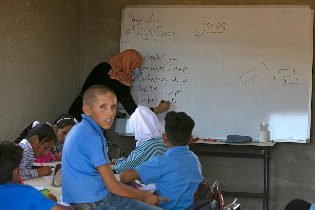 Palestinian students sit with their teacher inside a classroom at the Ras al-Tenneen school in eastern Ramallah city which an Israeli court ruled that it was built without the necessary construction permit and rejected an appeal against its imminent demolition, on 8 October 2020. [ABBAS MOMANI/AFP via Getty Images]