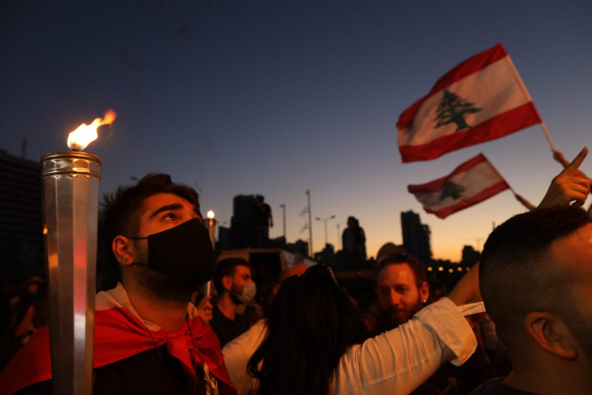 People hold Lebanese flags and lit candles to mark the one-year anniversary of anti-government protests on October 17, 2020 in Beirut, Lebanon [Marwan Tahtah/Getty Images]