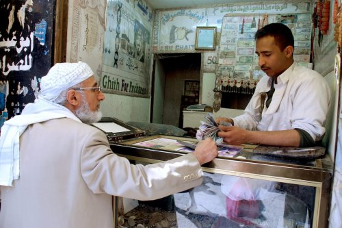 A Yemeni money changer serves a customer at his small shop in Sanaa, on 20 January 2010. [AFP via Getty Images]
