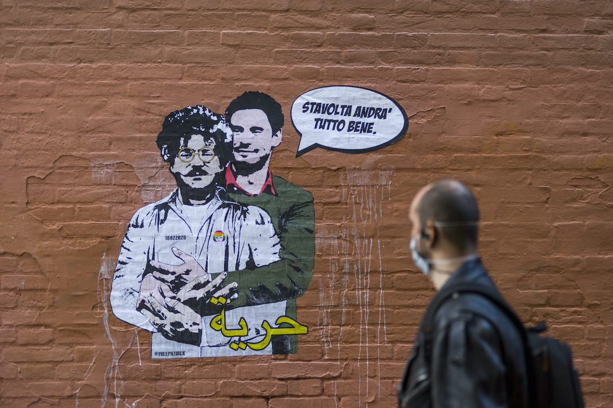 A person walks by the mural created by the artist Laika a few metres from the Rectorate of the University of Bologna, to ask for Patrick Zaki's release a few days before the trial on October 05, 2020 in Bologna, Italy. [Michele Lapini/Getty Images]