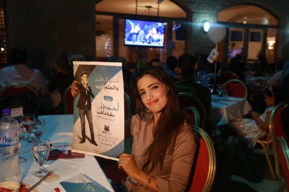 A Palestinian supporter of Mohammed Assaf, a Palestinian finalist on the Arab Idol talent show, holds his poster in Gaza City as she watches his televised performance late on June 21, 2013. Since March, the 22-year-old Gazan's powerful voice has propelled him to the final of a Beirut-based competition that started out with 27. AFP PHOTO/MOHAMMED ABED (Photo credit should read MOHAMMED ABED/AFP via Getty Images)