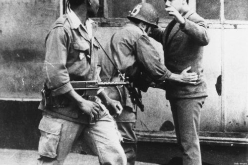 21st March 1962: French soldiers search a civilian in an Algiers street, during the Algerian War of Independence. (Photo by Central Press/Getty Images)