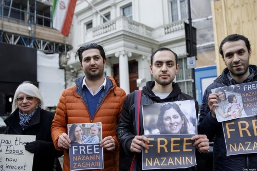 Campaigners hold posters as Richard Ratcliffe, husband of jailed British-Iranian woman Nazanin Zaghari-Ratcliffe, delivers a petition and a letter addressed to the Iranian Deputy Foreign Minister Abbas Araghchi to demand her release, at the Iranian Embassy in London on February 21, 2018. [TOLGA AKMEN/AFP via Getty Images]