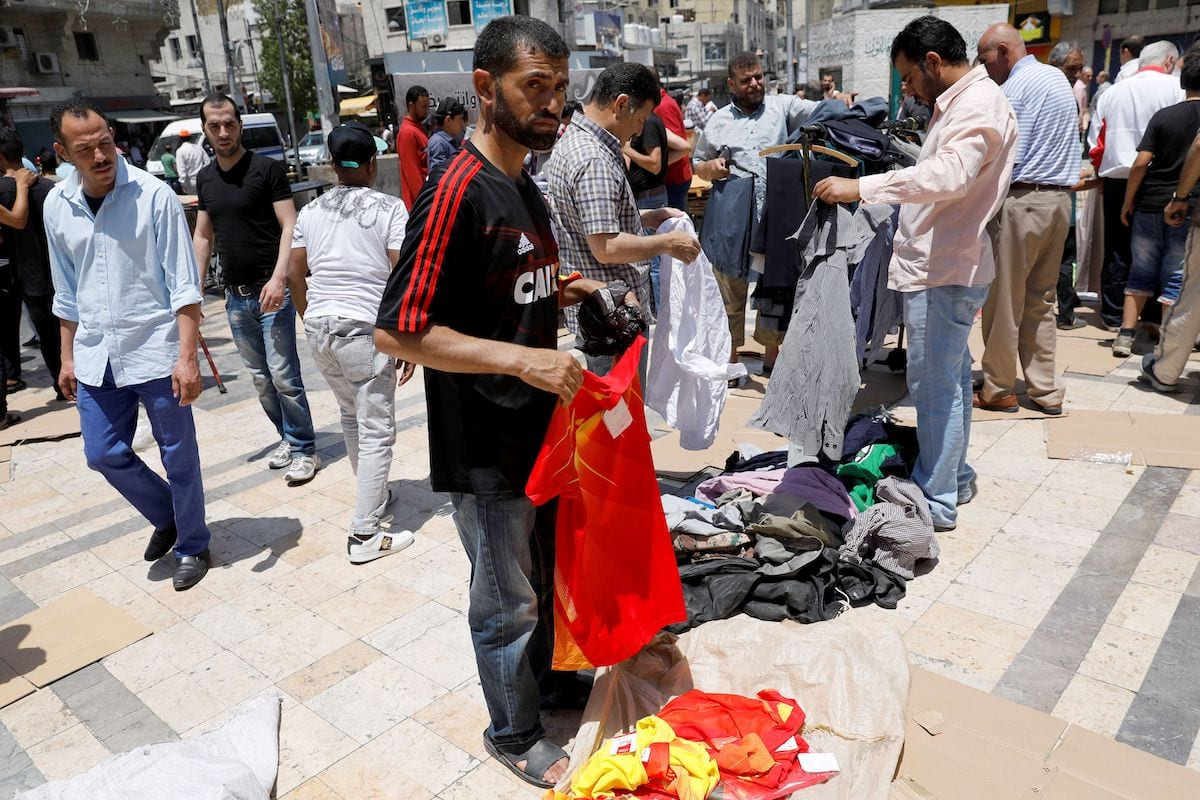 Jordanians buy second-hand clothes in an open air market in central Amman on 8 June 2018. [AHMAD GHARABLI/AFP via Getty Images]