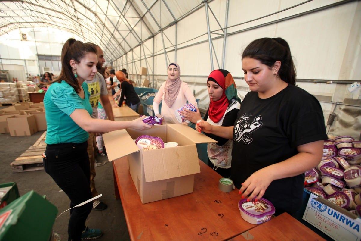 Palestinians prepare the food aid in Jerusalem on 5 August 2014 [Saeed Qaq/ApaImages]