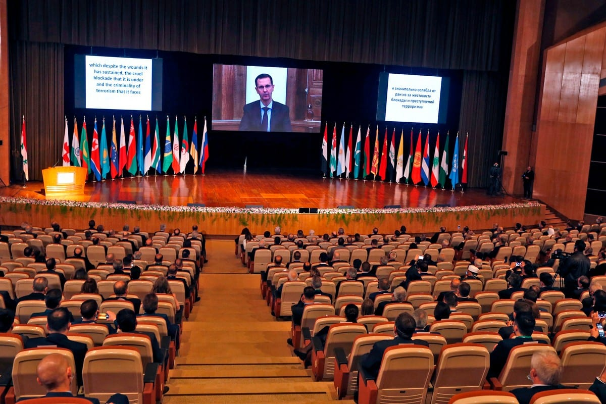 Syria's President Bashar Al-Assad (on screen) at the international conference on the return of refugees held in Damascus on 11 November 2020 [LOUAI BESHARA/AFP/Getty Images]