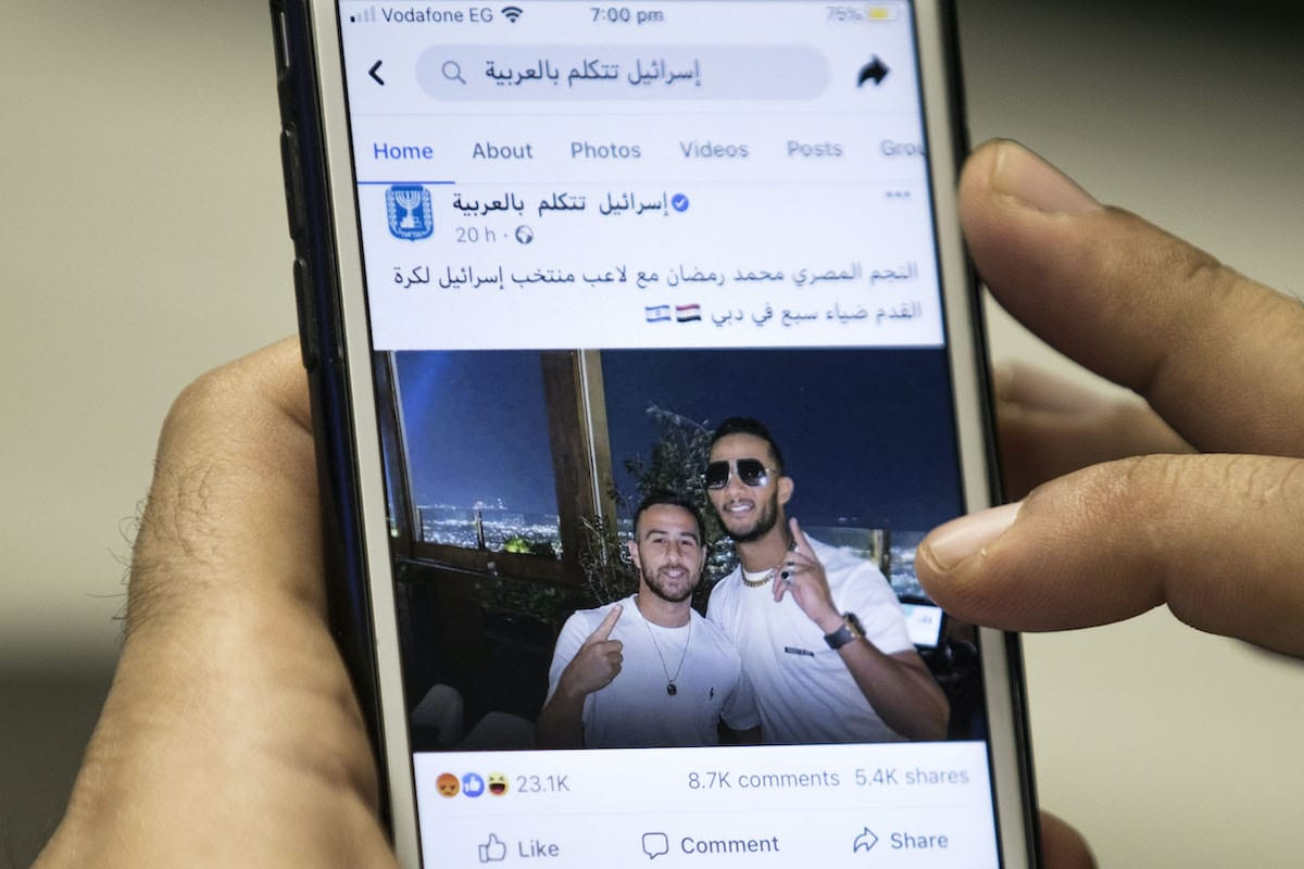 "A man holds a phone showing a picture of Egypt's self-proclaimed ""superstar"" Mohamed Ramadan posted by the official Facebook page of the State of Israel in Arabic (linked to the foreign ministry) depicting Ramadan (R) hugging Israeli midfielder Dia Saba in Dubai on 22 November 2020 [KHALED DESOUKI/AFP via Getty Images]"