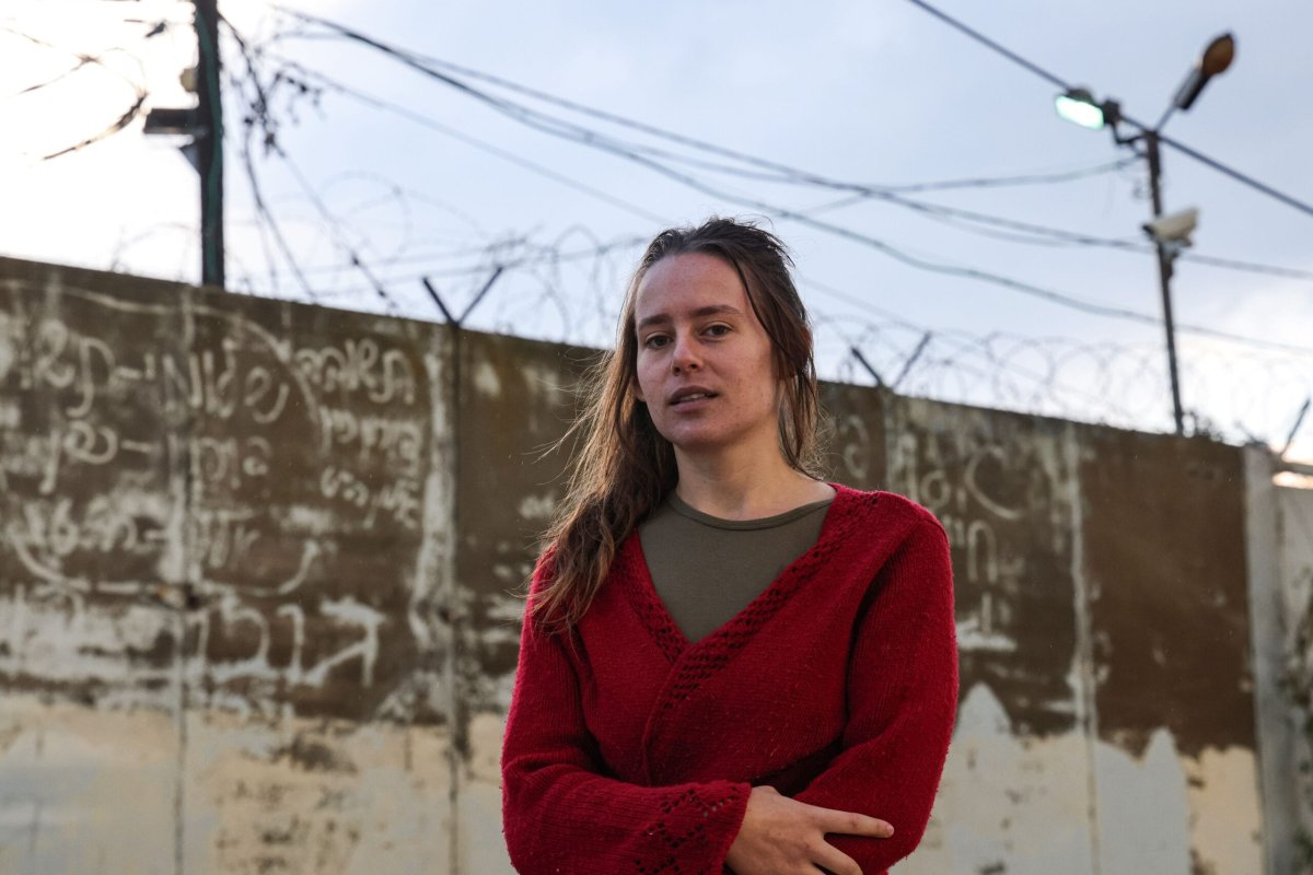 "Hallel Rabin, a 19-year-old Israeli conscientious objector, poses for a picture outside the ""number six"" military prison near Atlit in northern Israel on November 20, 2020, upon release from jail for refusing to serve in the Israeli army. - Army service is compulsory for most Israeli citizens and while many seek exemptions on various grounds -- some arguably less than truthful -- Rabin's case is unusual in that she openly declared herself to be a pacifist and served prison time. Hallel had served a total of 56 days since August at the grim military prison ""number six"", and was facing up to 80 more in detention. But after grilling her at four hearings, an army board finally accepted that her pacifism was sincere and not driven by ""political considerations,"" which would have landed her more prison time. (Photo by Emmanuel DUNAND / AFP) (Photo by EMMANUEL DUNAND/AFP via Getty Images)"
