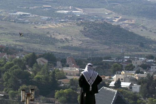 A Palestinian man looks towards the Israeli settlement of Shavei Shomron built next to the Palestinian village of Naqoura, west of Nablus in the occupied West Bank, on 23 November 2020. [JAAFAR ASHTIYEH/AFP via Getty Images]