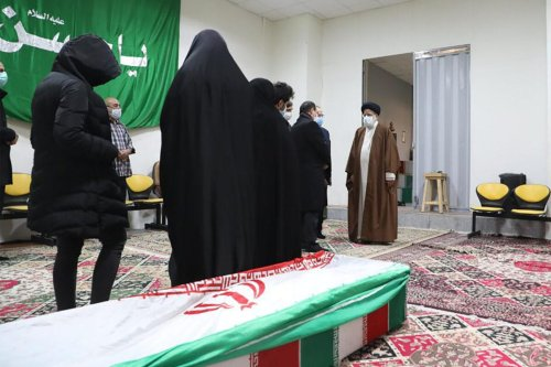 "Iran's Judiciary Chief Ayatollah Ebrahim Raisi (R) pays respects to the body of slain scientist Mohsen Fakhrizadeh among his family, in the capital Tehran on November 28, 2020. - Mohsen Fakhrizadeh, dubbed by Israel as the ""father"" of Iran's nuclear programme, died on November 27 after being seriously wounded when assailants targeted his car and engaged in a gunfight with his bodyguards outside Tehran, according to Iran's defence ministry. The assassination comes less than two months before US President-elect Joe Biden is due to take office, after a tumultuous four years of hawkish foreign policy in the Middle East under President Donald Trump. (Photo by - / MIZAN NEWS AGENCY / AFP) (Photo by -/MIZAN NEWS AGENCY/AFP via Getty Images)"