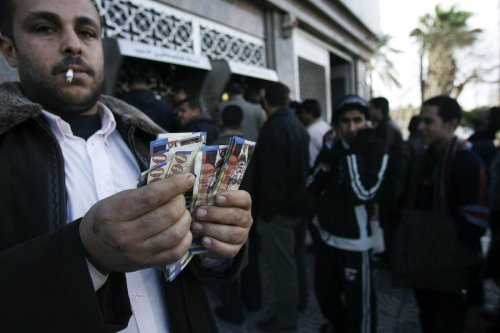 Palestinian employee shows his salary while others stand beside ATM machines in Gaza city, Gaza Strip on January 28, 2007 [Abid Katib/Getty Images]