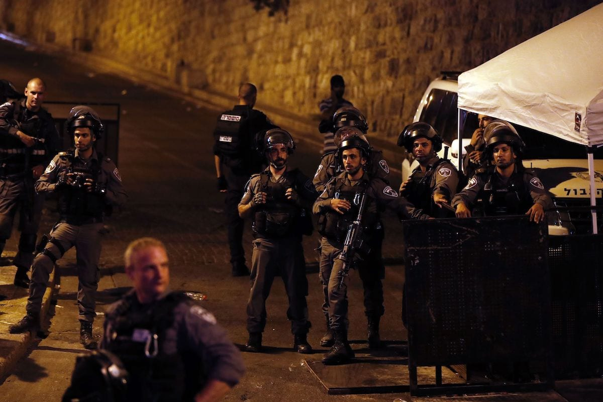 Israeli security forces stand by as Palestinian Muslim worshippers pray outside Lions' Gate, a main entrance to the Al-Aqsa mosque compound in Jerusalem's Old City, on 24 July 2017 [AHMAD GHARABLI/AFP via Getty Images]