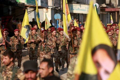 Kurdish People's Protection Units (YPG) military police members demonstrate with their flags and others bearing the portrait of Kurdistan Worker's Party (PKK) leader Abdullah Ocalan in the Kurdish town of Al-Muabbadah in the northeastern part of Hassakah province on 24 February 2018 [DELIL SOULEIMAN/AFP via Getty Images]