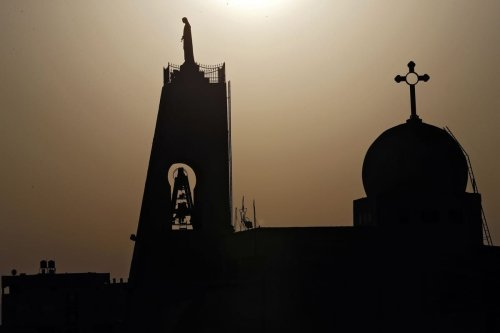 The sun sets behind a church in Nazareth on 18 September 2019 [AHMAD GHARABLI/AFP/Getty Images]