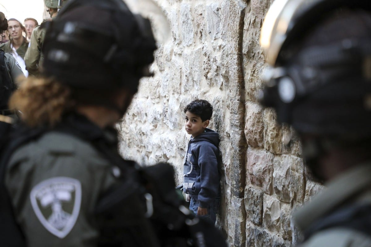 Israeli soldiers look at a Palestinian boy as he waits by the wall for Israeli settlers touring the old city and market of Hebron in the occupied West Bank to pass, on 21 December 2019. [HAZEM BADER/AFP via Getty Images]