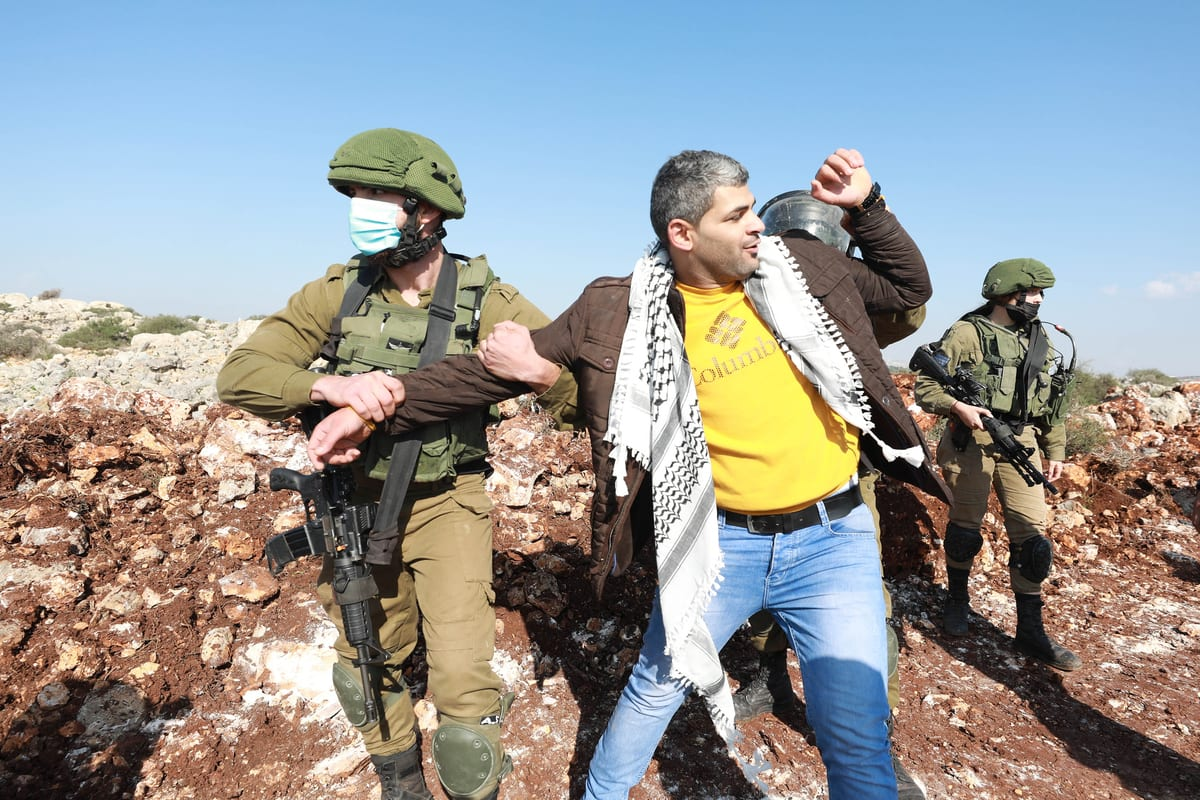 Israeli forces arrest a Palestinian as they intervene in Palestinians reacting to Jewish settlers for trying to seize agricultural lands of Palestinians in al-Ras region in Selfit, West Bank on November 30, 2020 [Issam Rimawi/Anadolu Agency]